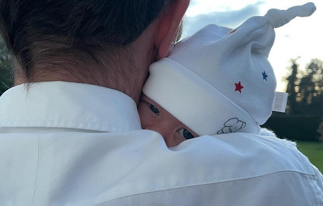 August wearing a personalised cardigan with his name embroidered on the back, and a hat with blue and red stars from Jojo Maman Bebe