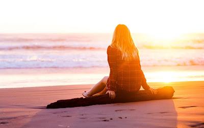 Chica rubia sentada en un tronco sobre la arena en la playa