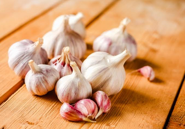 What are the benefits of swallowing garlic on an empty stomach for slimming?