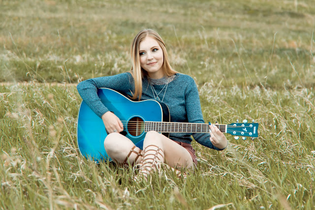 a young woman plays the guitar in a grassy meadow in Boulder Colorado for her Senior Portraits