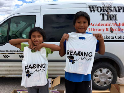 "two boys holding up ""reading ninja"" book bags in front of Woksape Tipi  Academic Public Library Archives Oglala Lakota College Van"