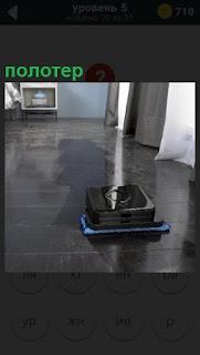 В комнате осуществляет уборку автоматический полотер робот