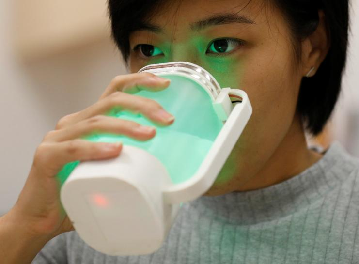 An NUS student tastes a virtual lemonade simulator, which uses electrodes to mimic the flavour and LED lights to imitate the color of real lemonade, at the National University of Singapore campus in Singapore April 13, 2017.