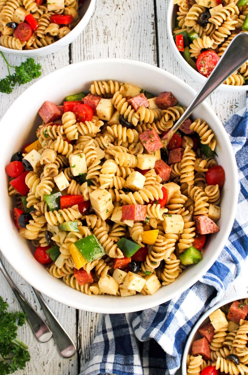 Top view of Manhattan Deli Pasta salad in a large white bowl with a blue and white checkered napkin next to it on a white wood background.