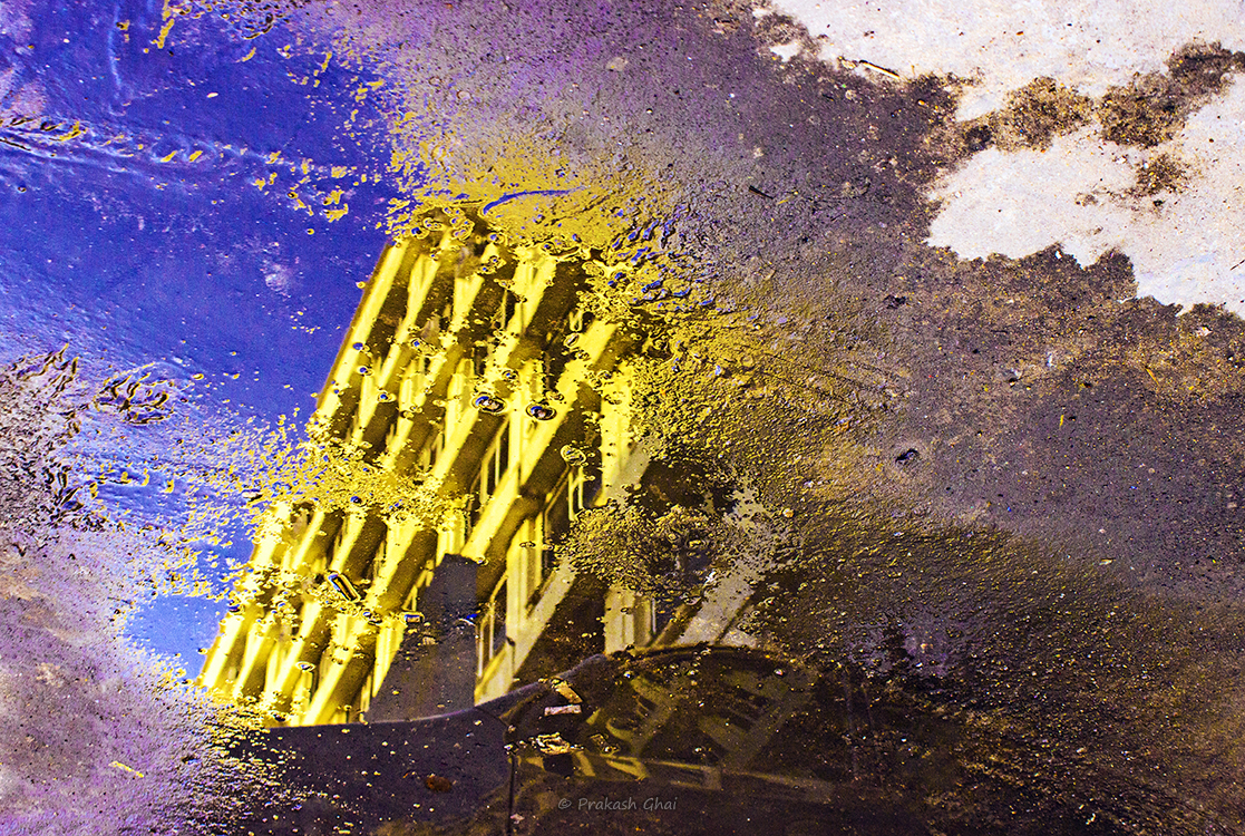 A Minimalist Photo of Reflection of a yellow building in a puddle of water at ganpati plaza jaipur