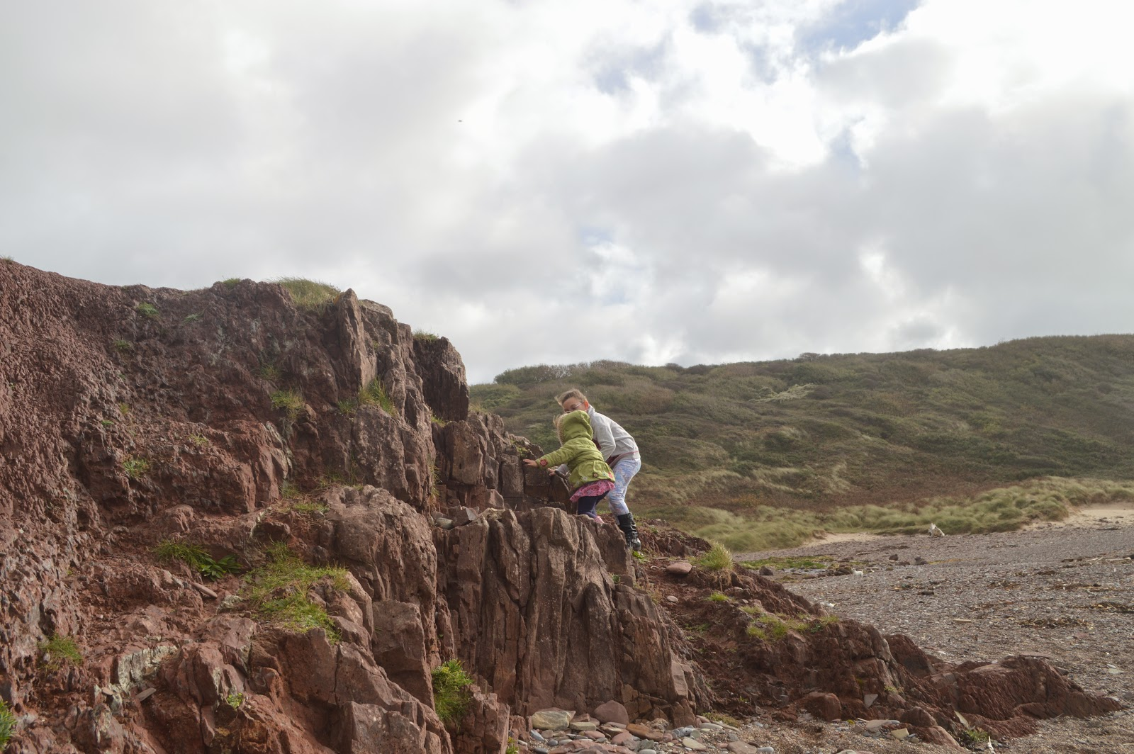 Girls Climbing Rocks at Manorbier Beach, Pembrokeshire, Wales