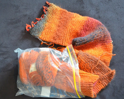 An unfinished scarf in warm reds, oranges, and charcoal looks like it is trying to shuffle out of a plastic snap-lock bag.  The working row is covered wihth red stitch markers.