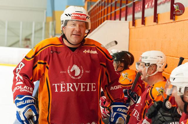 Hokejists uz komandas soliņa kopā ar komandas biedriem