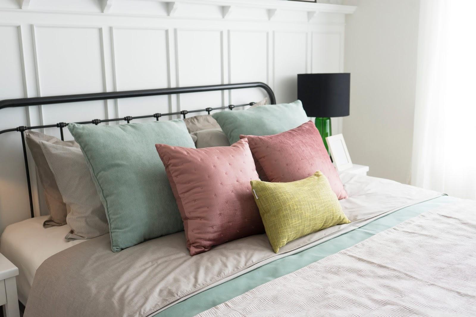 Cama de hierro con ropa en tonos claros (verde, rosa, beige)