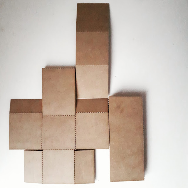 Aerial view of a 1/12 scale miniature cardboard chair kit, spread out to look like a game of Tetris.