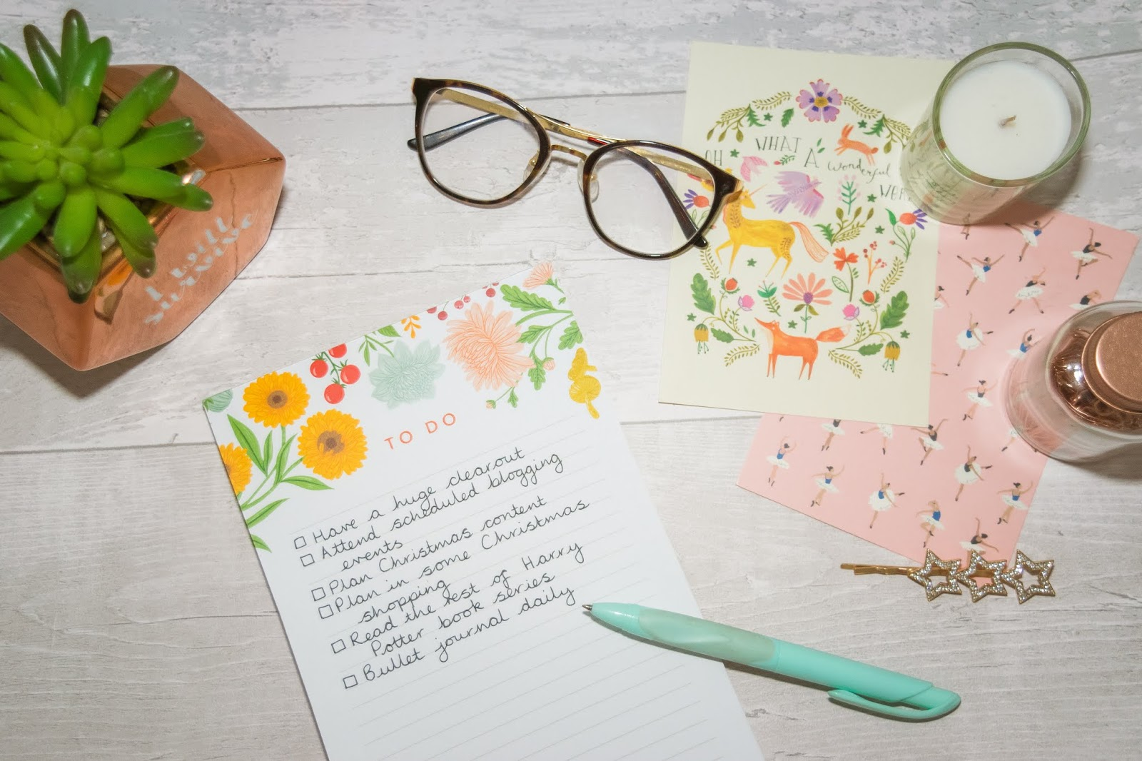 Flatlay photograph of a list pad with a faux succulent in a copper pot on the top left hand corner, two autumnal themed postcards on the top right with a white candle and a pot of copper paperclips on top and tortoise shell aviator glasses above the list pad.
