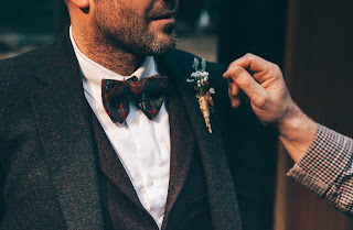 A men appreciating the design of boutonniere of other men's suit.