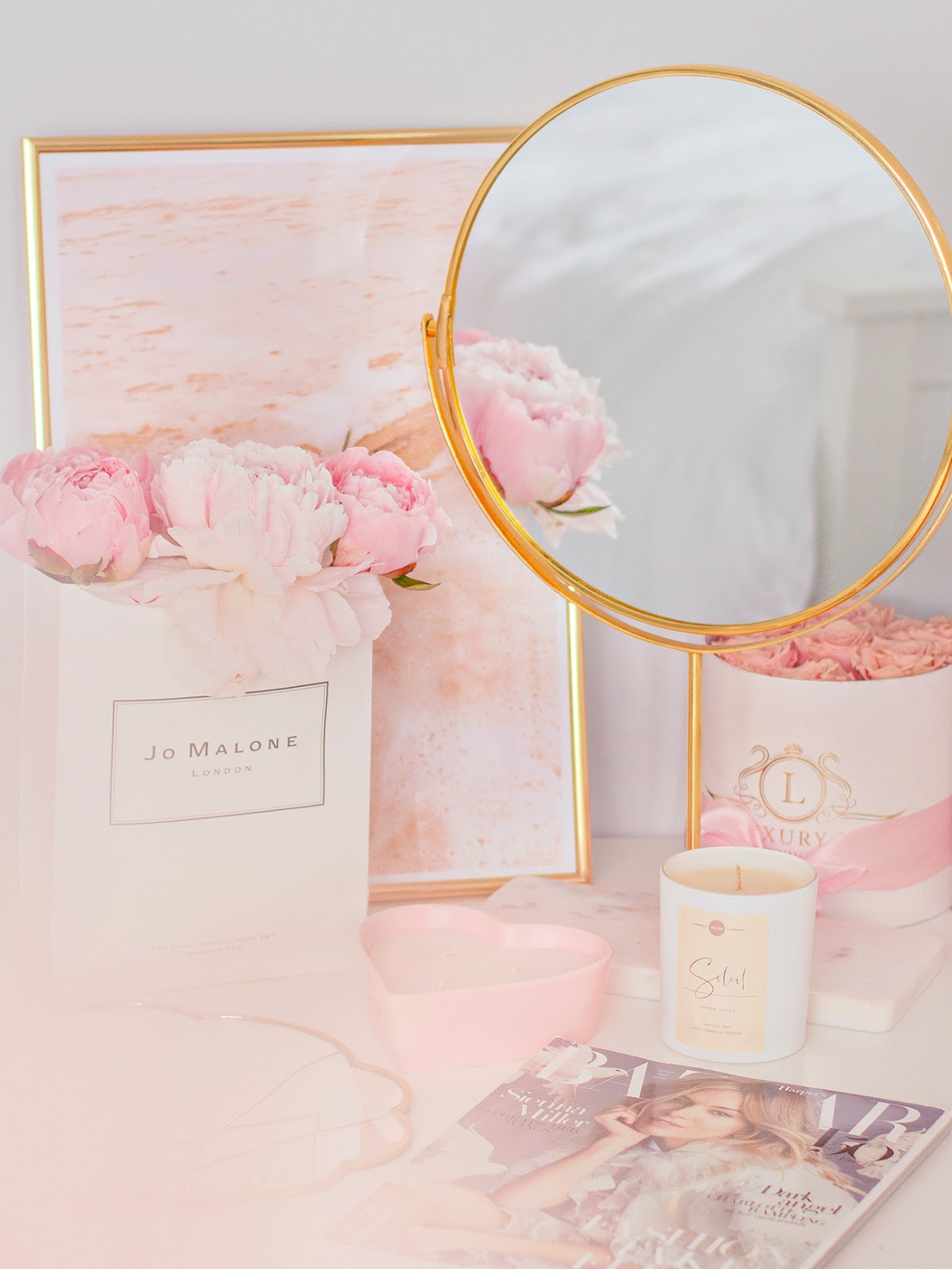 Desk with a round gold mirror and pink peonies in a bag