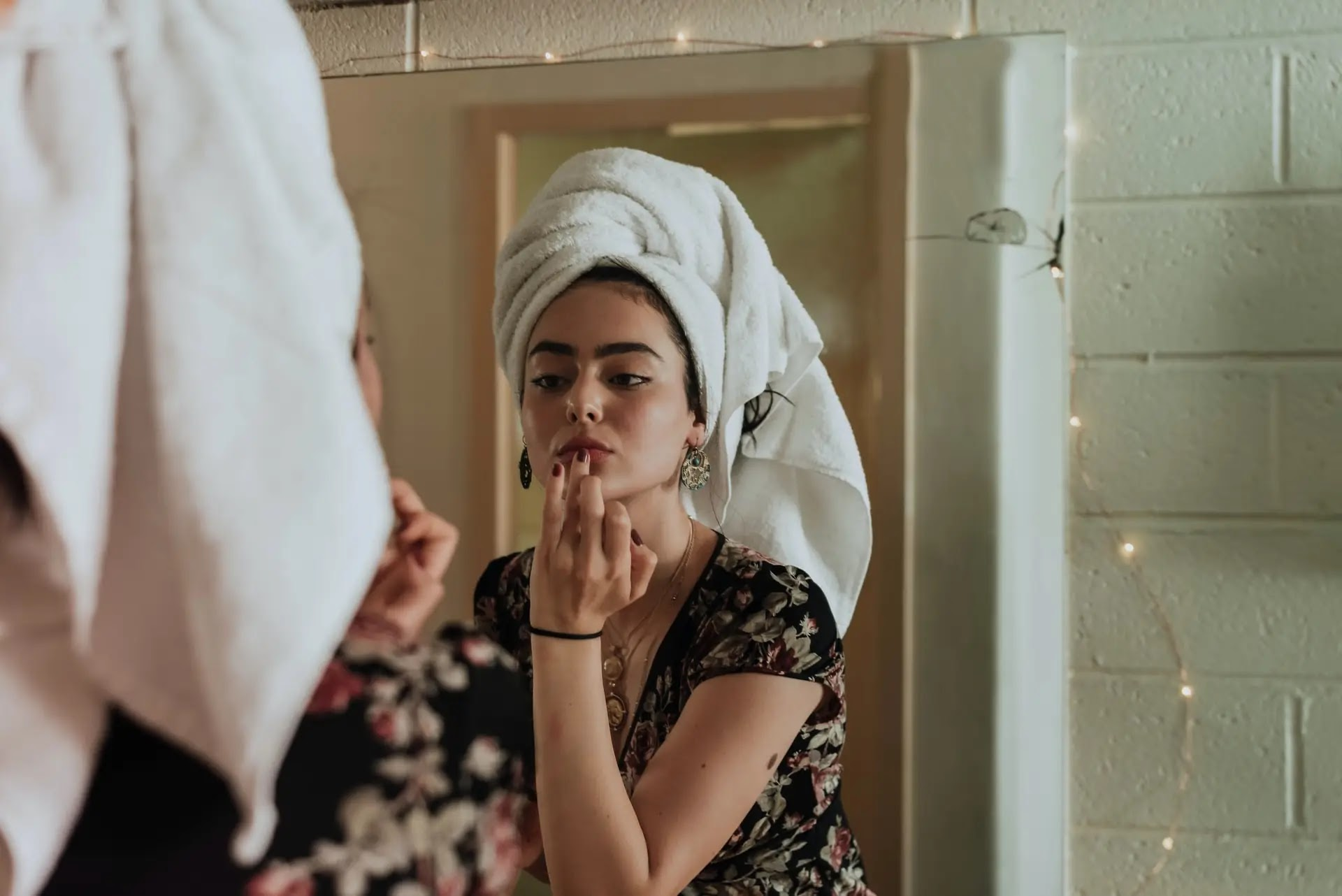 aprende ingles chica joven se da brillo de labios frente al espejo