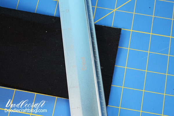 Step 2: Black Felt Buntings Then get 4 pieces of black felt. These pieces measure 9x12 inches. Fold it in half and place the ruler at the bottom edge. Place it right on the open ended corners and angle the ruler up 1.5 inches to the folded center.