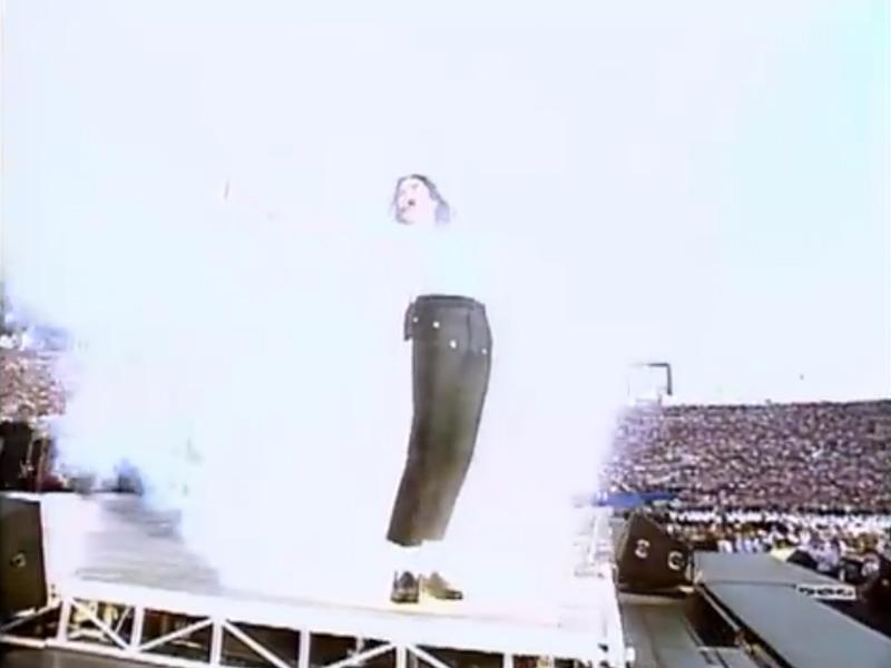 煙の中で両手を上げて背を反らしたマイケル・ジャクソン