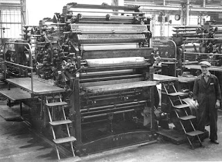 Black and white image of a large industrial printing press machine, 1946, multiple rollers, with steps either side for access. A man in overalls and a flatcap is standing to one side of the machine to show the scale - the machine is nearly two times his height.