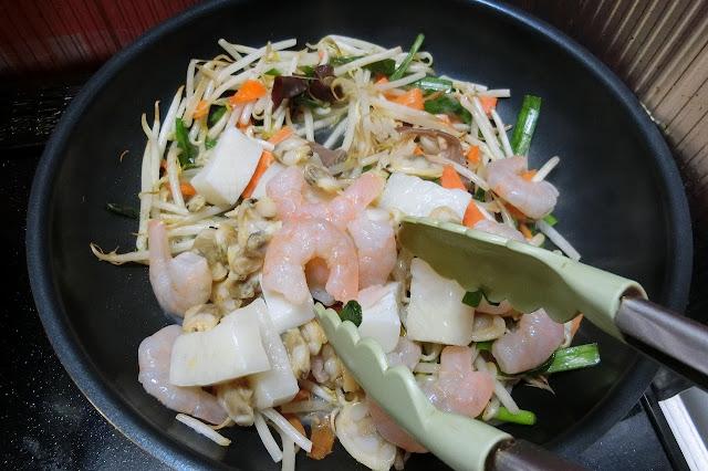 野菜に火が通ったら解凍したシーフードミックスを加え、エビの色が変わるまで炒め合わせます。