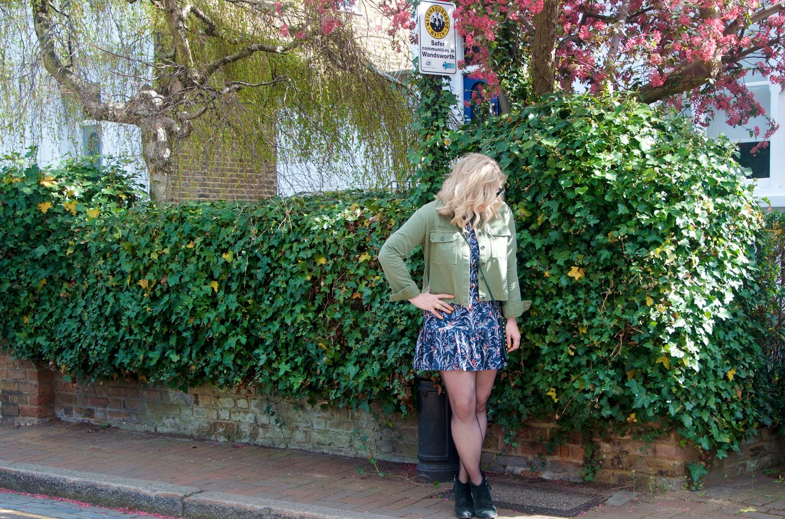 green jacket, floral dress, black boots, fishnet tights and spring flowers