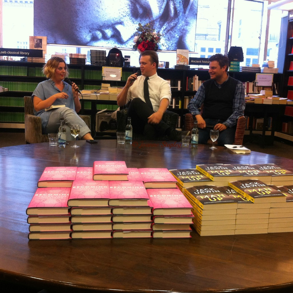 A photo of Laura Jane Williams, Jack Urwin and Joel Beckman at the Man Up Launch during their talk, sitting behind a table with stacks of Becoming and Man Up on it.