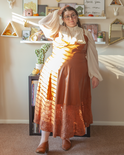 An outfit consisting of a cream Regency era inspired bishop sleeve blouse under a cognac brown midi dress and brown d'orsay flats