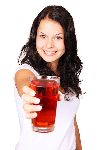 mujer joven sostien un vaso de infusión de arándano rojo con una sonrisa