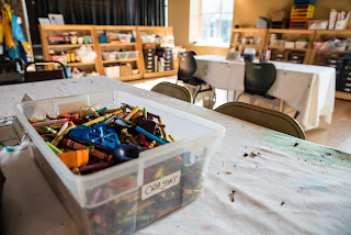 a plastic tub of crayons sits atop a table at the Museum of Visual Materials in Sioux Falls South Dakota