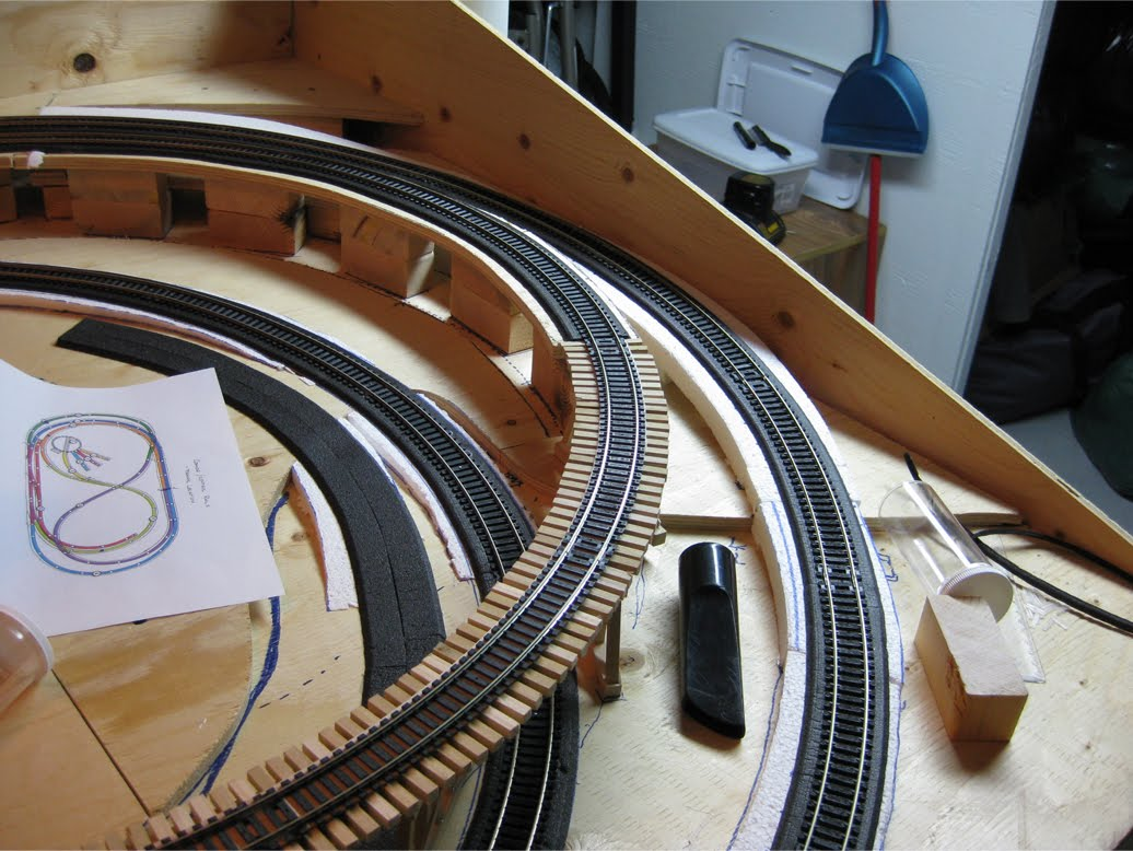 Track being installed onto foam roadbed and wooden train trestle