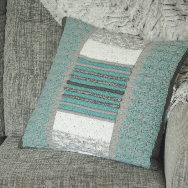 blue and grey knitted cushion on a grey sofa