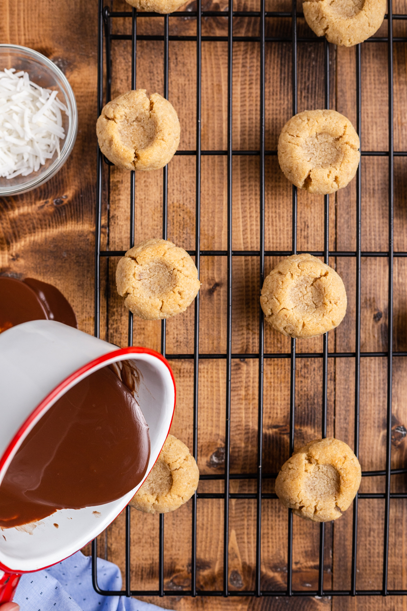 Over head photo of pouring the chocolate ganache into the cookies to make Keto Chocolate Thumbprint Cookies.