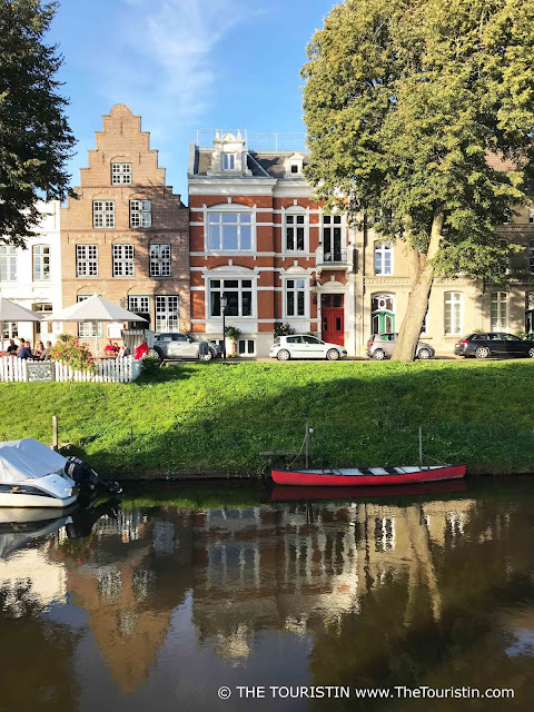 Gabled houses, trees and boats and their reflections in the canal