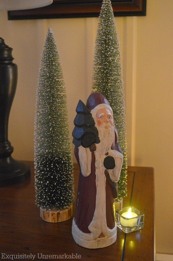 Bottle Brush Trees on a table with Santa statue and votive candle