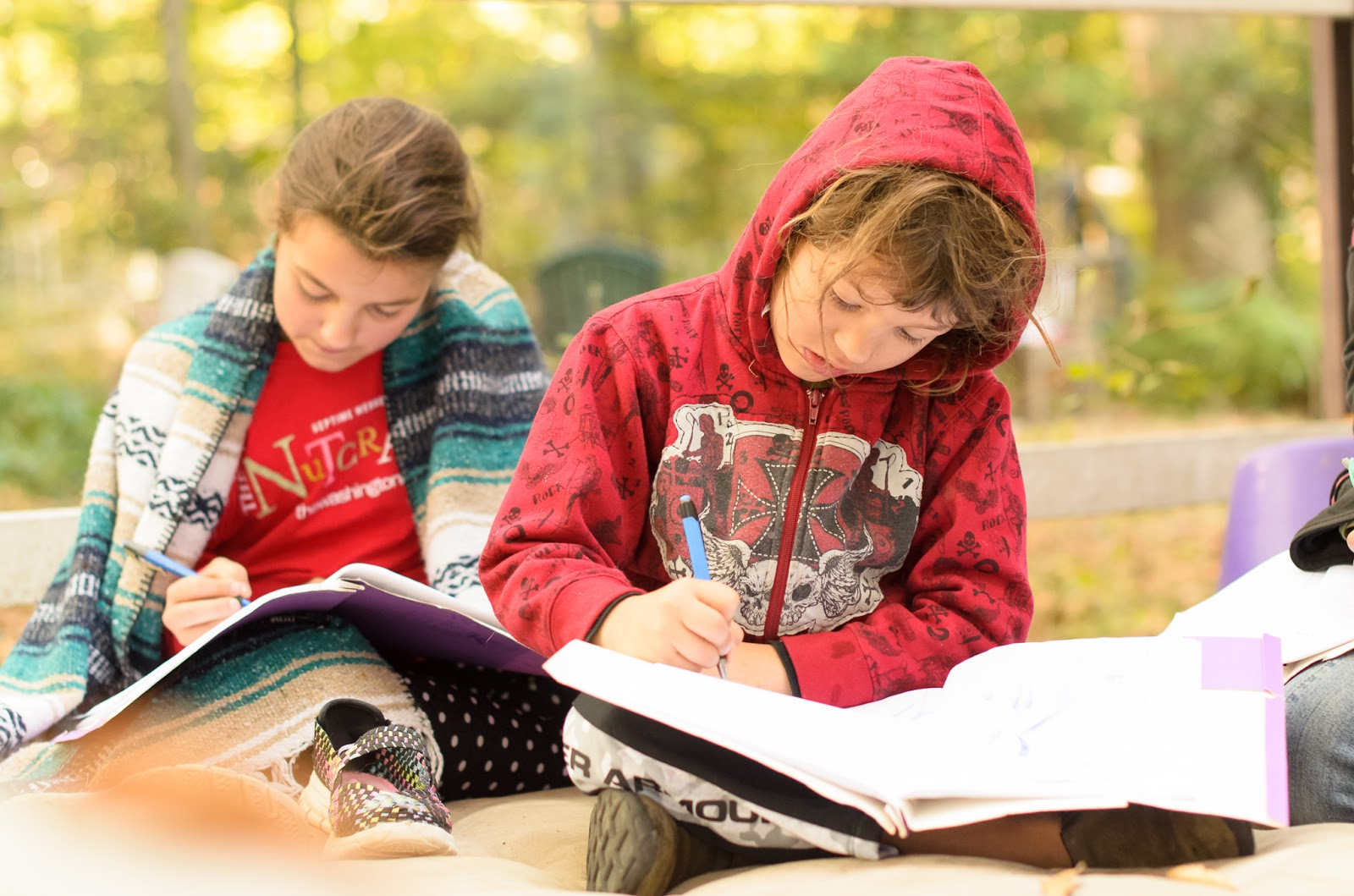 brother and sister writing in homeschooling lesson outside  ©Diana Sherblom Photography