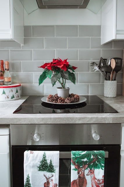 Electric hob with a poinsettia and Christmas tea towels