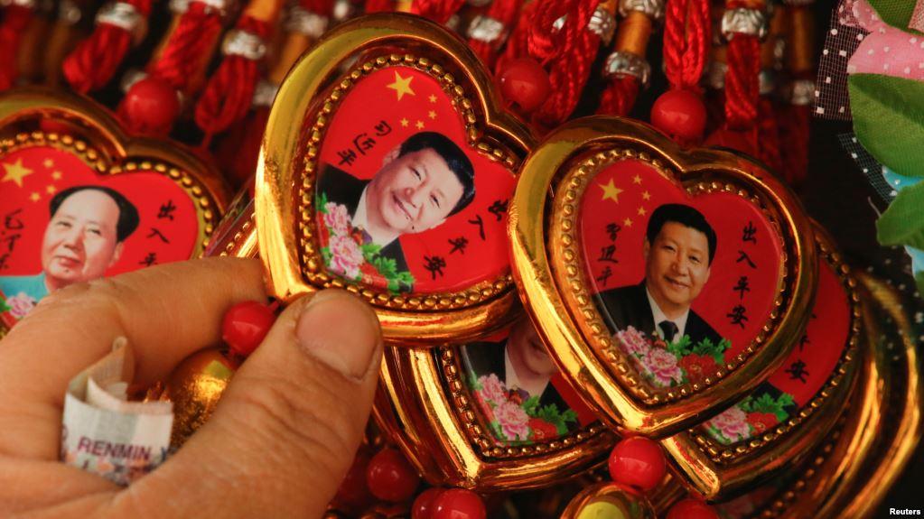 Una mujer escoge un recuerdo con el retrato del presidente chino Xi Jinping / REUTERS