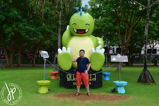 green cute monster statue, man in orange shorts and black shirt