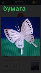 На сине зеленом фоне бумаги сделана и лежит красивая бабочка в виде заколки