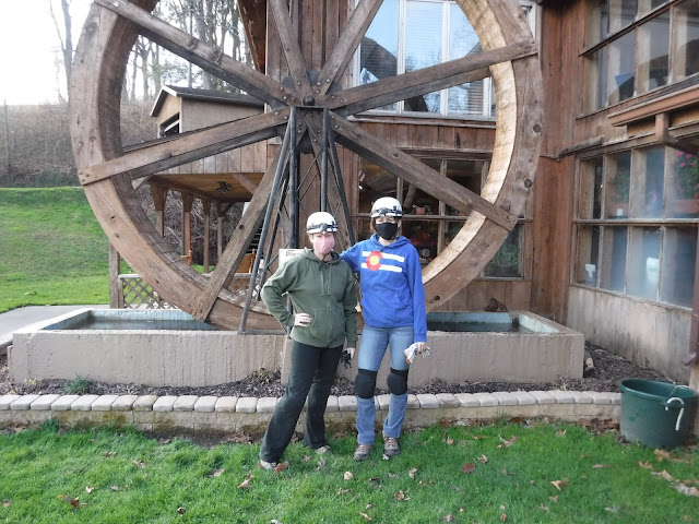 two women in front of old mill wheel