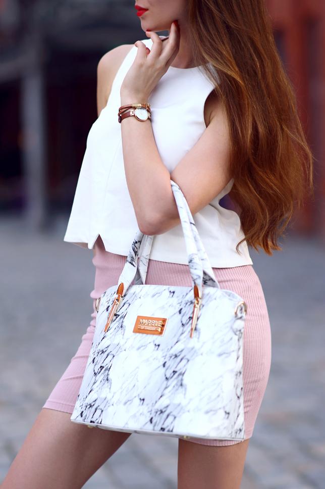 Biała bluzka, różowa obcisła spódniczka, biała wzorzysta torebka i beżowe sandały