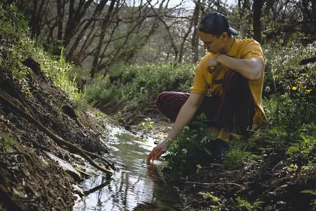 Jóven en el bosque sentado junto a un riachuelo tocando el agua con su mano derecha