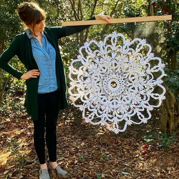 large-scale quilled doily held by its maker Griffin Carrick