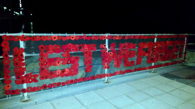 "Red poppies, crocheted and knitted, arranged to form the words ""LEST WE FORGET"" bordered by poppies on a rectangular mesh frame which is attached to the railings of Brighton Jetty."