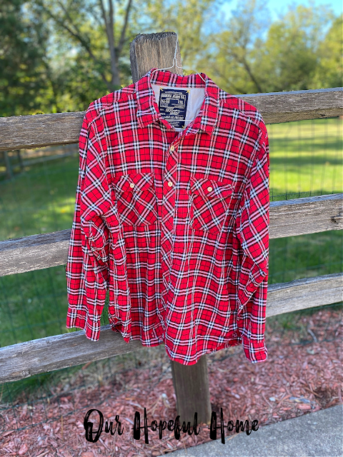 Nautica jeans Co. red plaid flannel shirt hanging on fence
