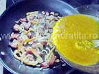 Omleta taraneasca cu sunca preparare reteta - turnam ouale cu branza in tigaie peste ceapa calita si ardei
