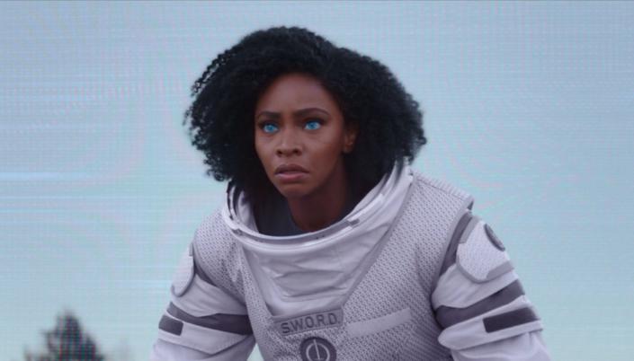 Imagem: Wanda vestida em um traje aeroespacial branco com um símbolo da S.W.O.R.D. no peito e os olhos azuis e brilhantes.