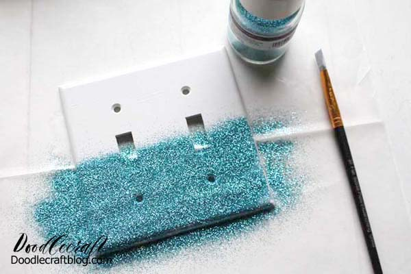 I used aqua glitter, my favorite color.  Then gently lift up the switch plate to dump all the excess glitter off onto the work surface.   Lift the paper and pour the glitter back into the jar.