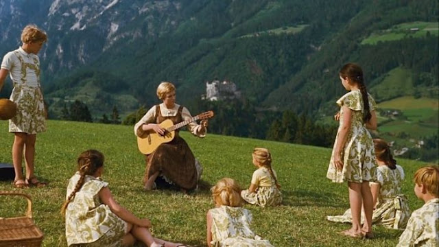 Julie Andrews and children in field in The Sound of Music