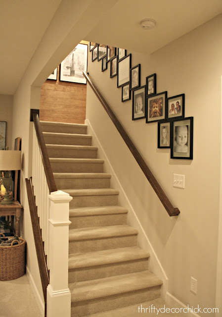 Gallery wall on stairs with wood accent wall