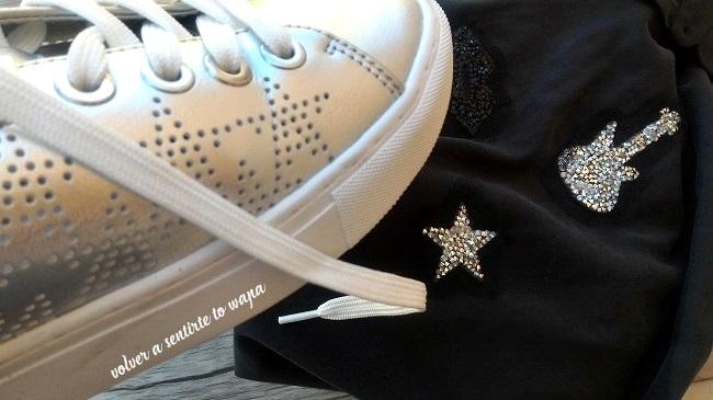 Camisa negra con parches de strass de Zara y deportivas plateadas con estrellas de Stradivarius