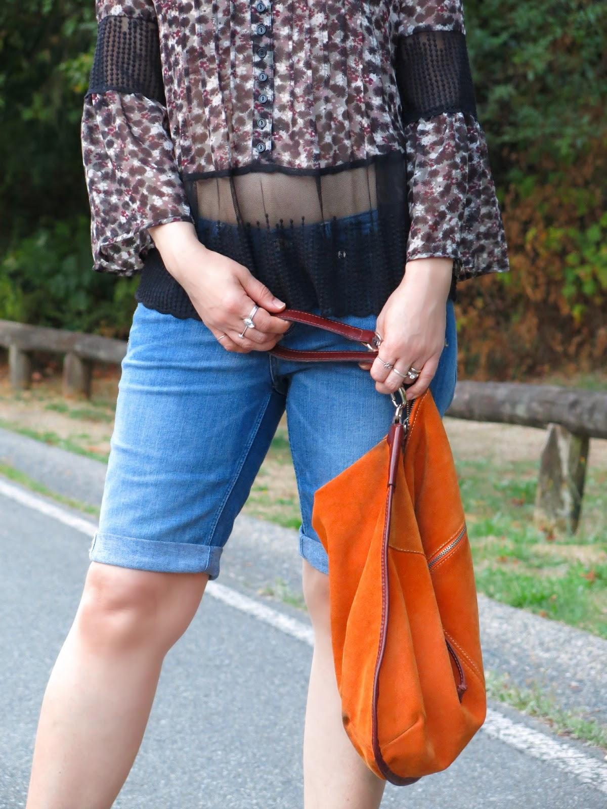 peasant blouse, denim bermuda shorts, and an orange suede bag